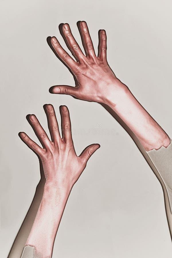 Αρσενικά χέρια που χρωματίζονται στο κόκκινο χρώμα στοκ φωτογραφία