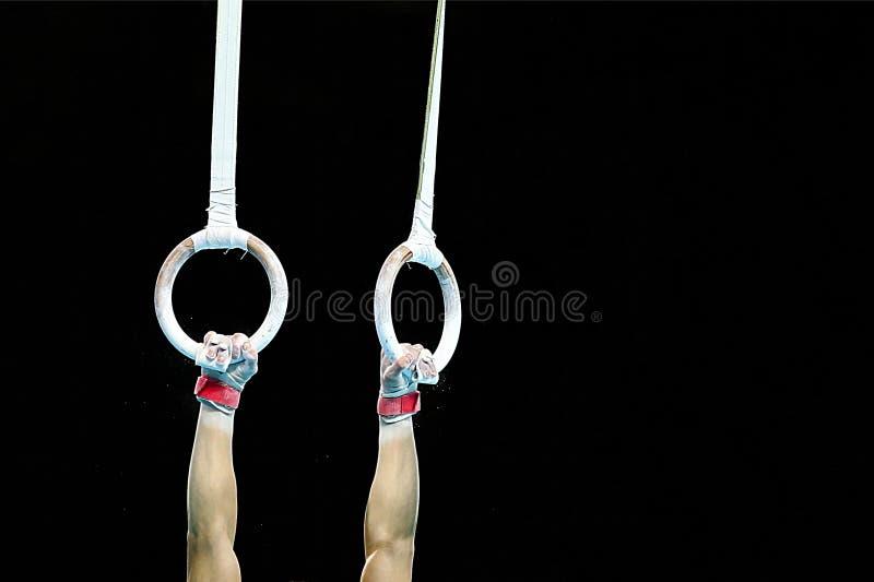 Αρσενικά gymnast χέρια που κρατούν τα δαχτυλίδια στοκ φωτογραφία