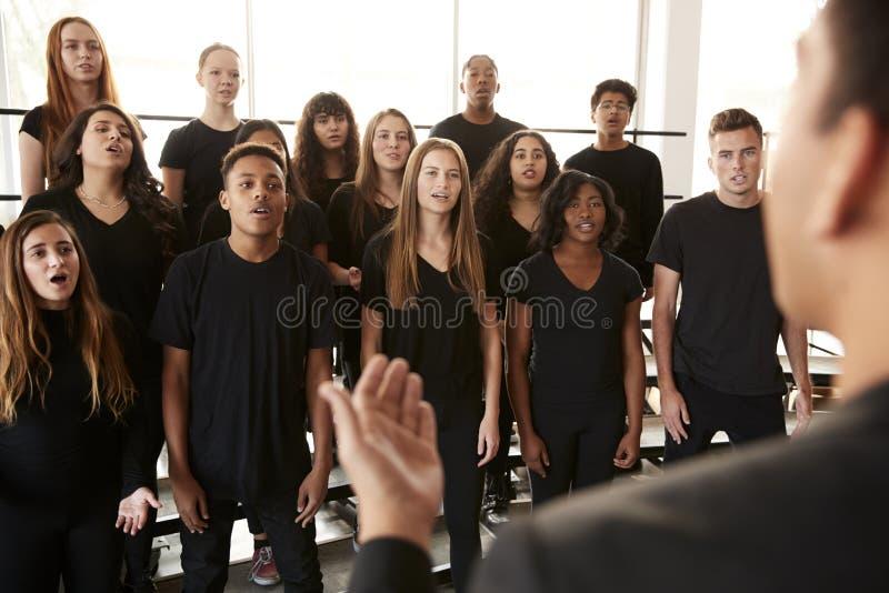 Αρσενικές και γυναίκες σπουδαστές που τραγουδούν στη χορωδία με το δάσκαλο στο σχολείο τεχνών προς θέαση στοκ εικόνα με δικαίωμα ελεύθερης χρήσης