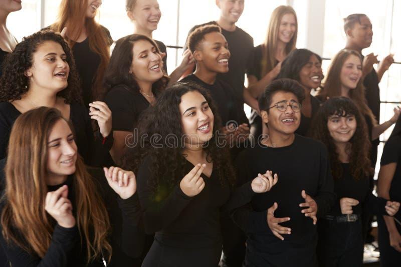 Αρσενικές και γυναίκες σπουδαστές που τραγουδούν στη χορωδία στο σχολείο τεχνών προς θέαση στοκ φωτογραφία