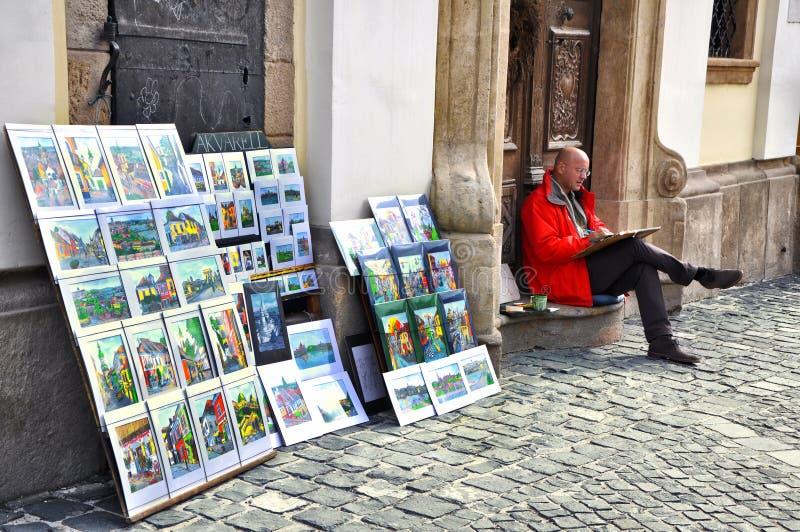 Αρσενικές πωλήσεις καλλιτεχνών τα έργα ζωγραφικής του στις οδούς Πολλοί καλλιτέχνες οδών σύρουν και πωλούν τα έργα ζωγραφικής στη στοκ εικόνες
