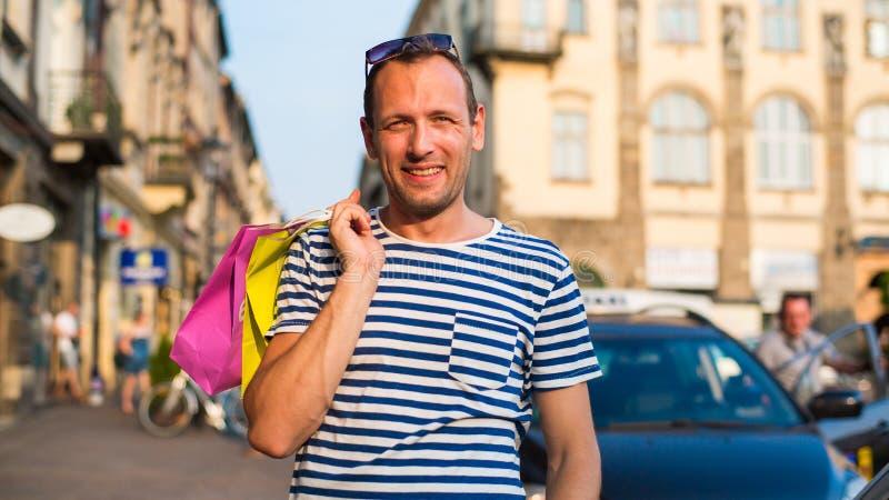 Αρσενικές τσάντες αγορών εκμετάλλευσης αγοραστών που φαίνονται πολύ ευτυχείς στοκ φωτογραφία με δικαίωμα ελεύθερης χρήσης