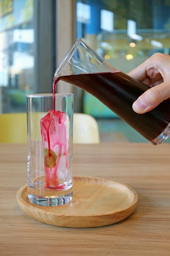 Αρσενική έναρξη χεριών στην έκχυση του χυμού Roselle επάνω σε έναν κύβο πάγου σε ένα γυαλί στον ξύλινο δίσκο στοκ εικόνα