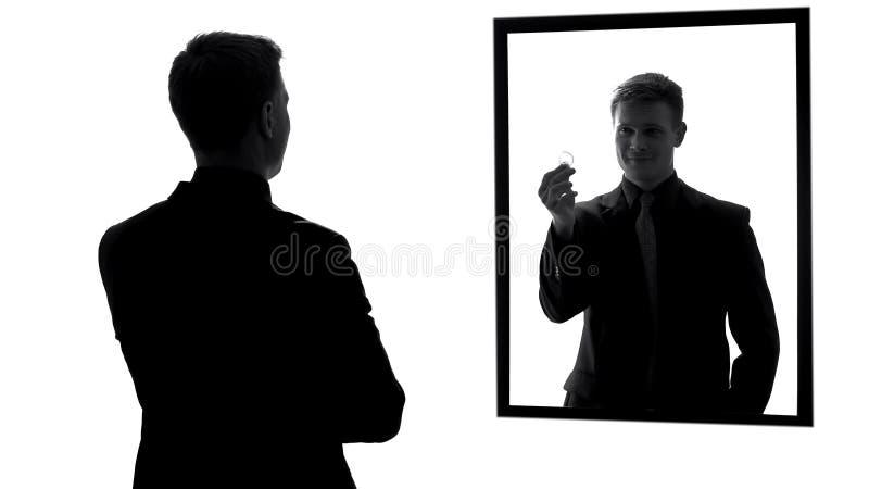 Αρσενική αντανάκλαση καθρεφτών που παρουσιάζει προφυλακτικό, προετοιμασία για την ημερομηνία, ευθύνη στοκ εικόνα με δικαίωμα ελεύθερης χρήσης