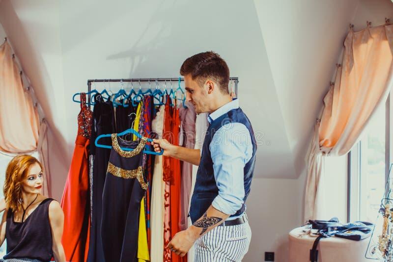 Αρσενική βοηθητική και νέα γυναίκα καταστημάτων στη μπουτίκ μόδας στοκ φωτογραφία με δικαίωμα ελεύθερης χρήσης