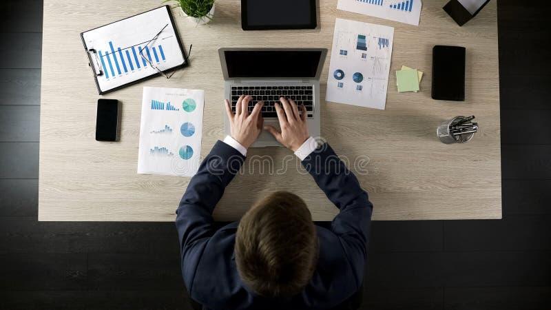 Αρσενική δακτυλογράφηση διευθυντή επιχείρησης στο lap-top, το πρόγραμμα προγραμματισμού ή τη επιχειρησιακή στρατηγική στοκ φωτογραφία