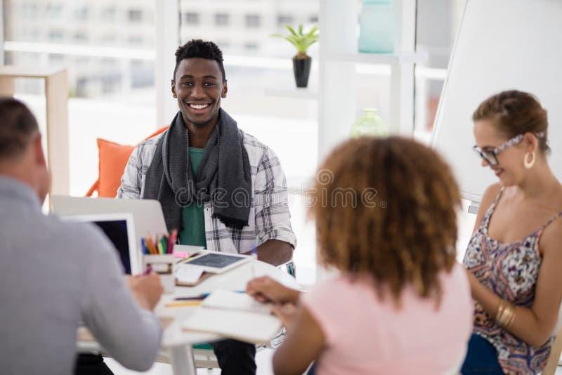 Αρσενική εκτελεστική συνεργασία με τους συναδέλφους του στο γραφείο στοκ φωτογραφίες