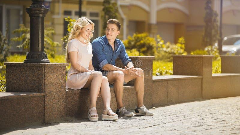 Αρσενική και θηλυκή συνεδρίαση στον πάγκο το ένα δίπλα στο άλλο, αδέξια, πρώτη ημερομηνία συναισθήματος στοκ εικόνα