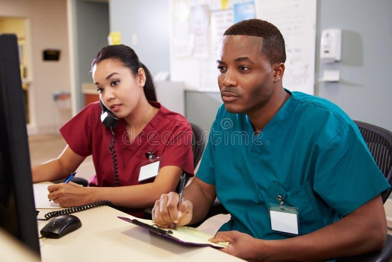 Αρσενική και θηλυκή νοσοκόμα που εργάζεται στο σταθμό νοσοκόμων στοκ φωτογραφία