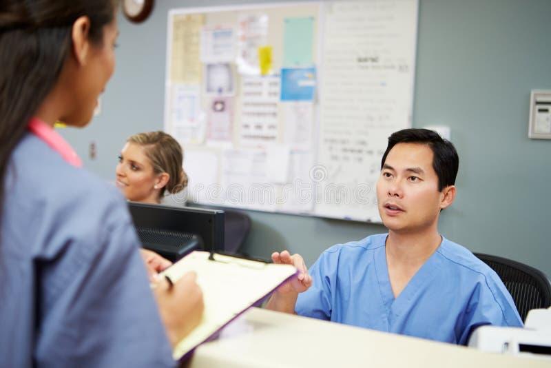 Αρσενική και θηλυκή νοσοκόμα στη συζήτηση στο σταθμό νοσοκόμων στοκ φωτογραφία με δικαίωμα ελεύθερης χρήσης