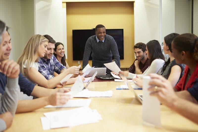 Αρσενική κύρια εξετάζοντας συνεδρίαση γύρω από τον πίνακα αιθουσών συνεδριάσεων στοκ φωτογραφίες