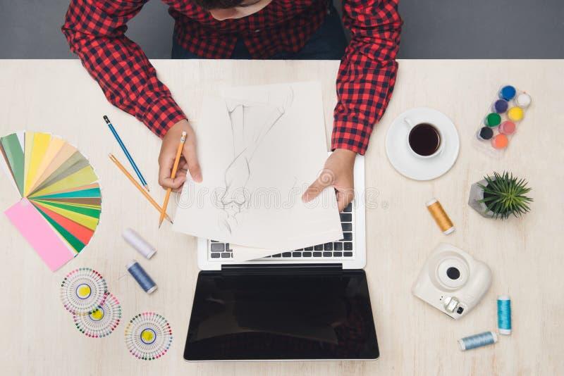 Αρσενική μόδα desginer που λειτουργεί στο γραφείο με τη μόδα sktech Κορυφή β στοκ φωτογραφίες