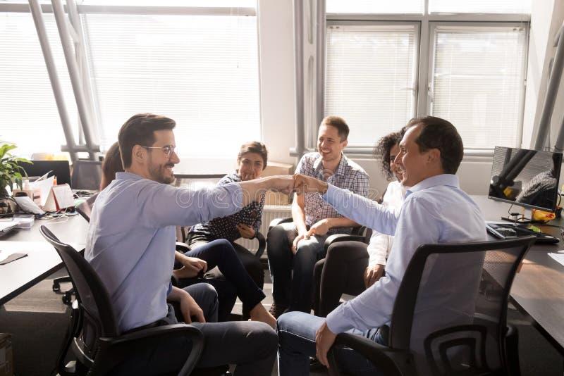 Αρσενική πρόσκρουση πυγμών συναδέλφων στη συνεδρίαση της επιχείρησης, επιχειρησιακή ενημέρωση στοκ εικόνες