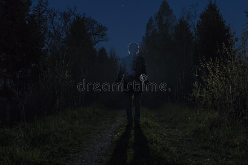 Αρσενική σκιαγραφία στη σκοτεινή δασική διάβαση μέσω των θάμνων στη νύχτα Άτομο που στέκεται στο δρόμο ενάντια στο αυτοκίνητο στοκ φωτογραφία με δικαίωμα ελεύθερης χρήσης