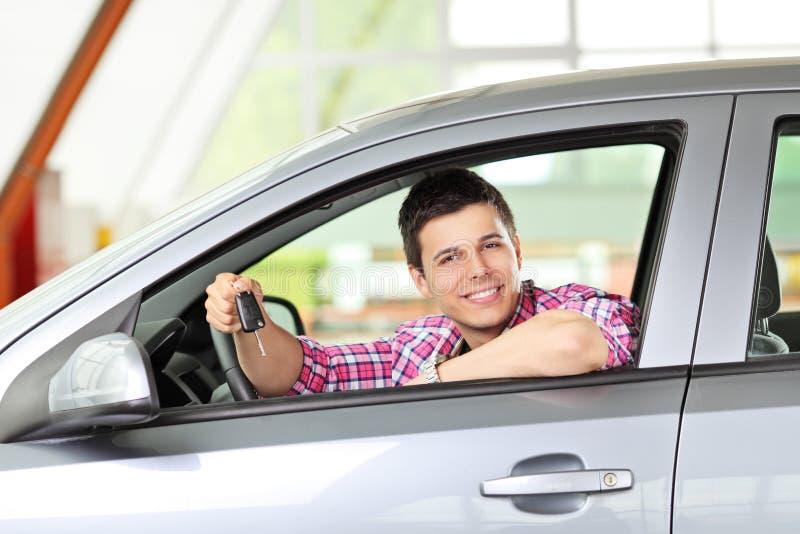 Αρσενική συνεδρίαση στο αυτοκίνητο και εκμετάλλευση ένα πλήκτρο στοκ εικόνες