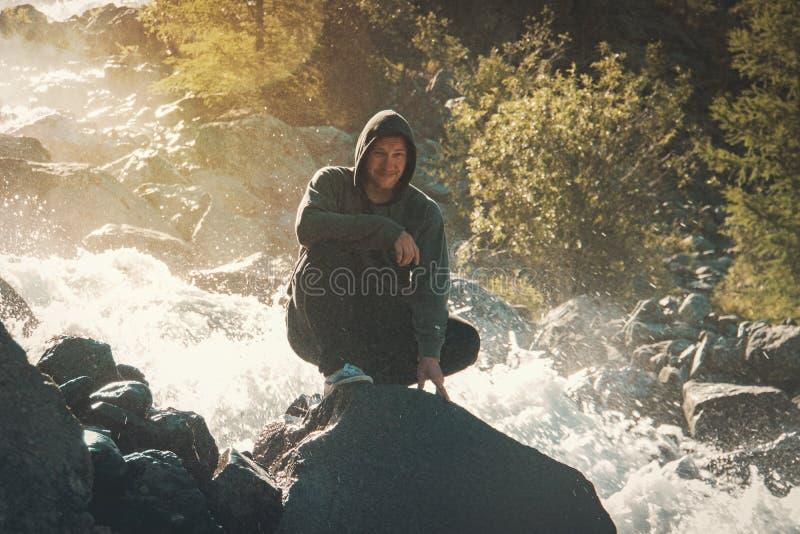 Αρσενική συνεδρίαση τουριστών σε έναν βράχο στο υπόβαθρο ενός καταρράκτη που περιβάλλεται από το καταβρέχοντας νερό Ο τύπος στηρί στοκ εικόνα με δικαίωμα ελεύθερης χρήσης