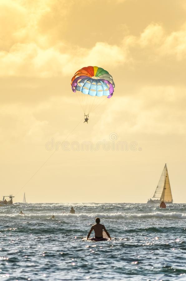 Αρσενική συνεδρίαση surfer στον πίνακά του που εξετάζει ένα parasailing αλεξίπτωτο ουράνιων τόξων στη Χαβάη στοκ εικόνες