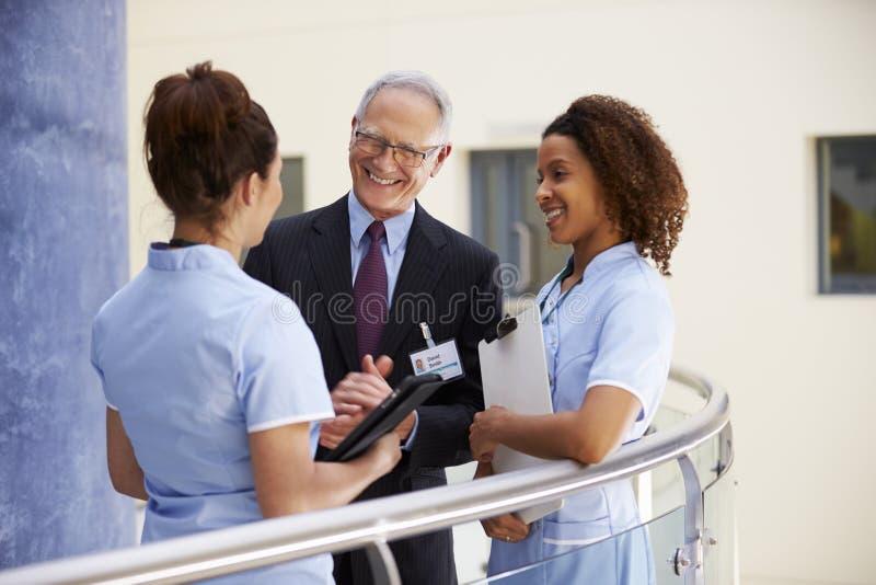 Αρσενική συνεδρίαση των συμβούλων με τις νοσοκόμες που χρησιμοποιούν την ψηφιακή ταμπλέτα στοκ φωτογραφίες