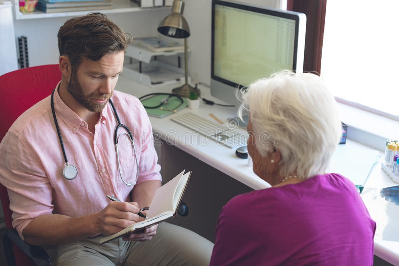 Αρσενική συνταγή γραψίματος γιατρών για την ανώτερη γυναίκα στο δωμάτιο κλινικών στοκ εικόνες