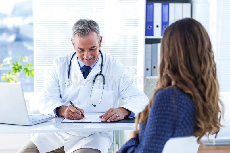 Αρσενική συνταγή γραψίματος γιατρών για τη γυναίκα στο νοσοκομείο στοκ φωτογραφίες με δικαίωμα ελεύθερης χρήσης