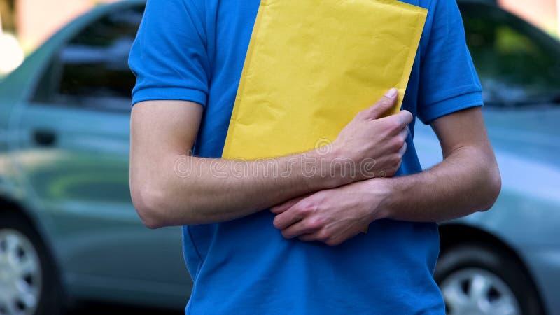 Αρσενική συσκευασία εκμετάλλευσης αγγελιαφόρων με τα έγγραφα, από σπίτι σε σπίτι ναυτιλία προστασίας στοκ εικόνες