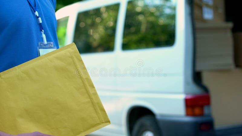 Αρσενική συσκευασία εκμετάλλευσης αγγελιαφόρων με τα έγγραφα, ταχυδρομική υπηρεσία, σαφής παράδοση στοκ φωτογραφίες