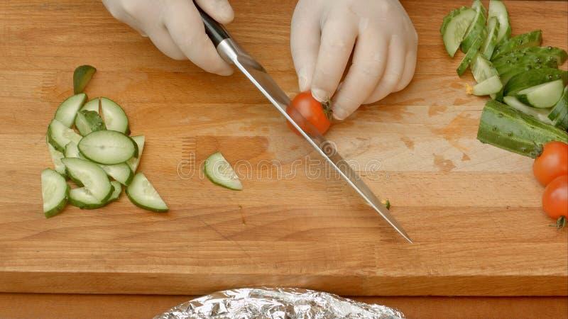 Αρσενική τέμνουσα ντομάτα χεριών αρχιμαγείρων στον τέμνοντα πίνακα με το αιχμηρό μαχαίρι στοκ εικόνες με δικαίωμα ελεύθερης χρήσης