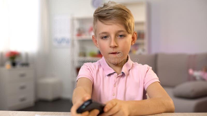 Αρσενική τηλεόραση προσοχής παιδιών που σύρει αντ' αυτού, μεταβαλλόμενος τηλεχειρισμός καναλιών στοκ φωτογραφία με δικαίωμα ελεύθερης χρήσης