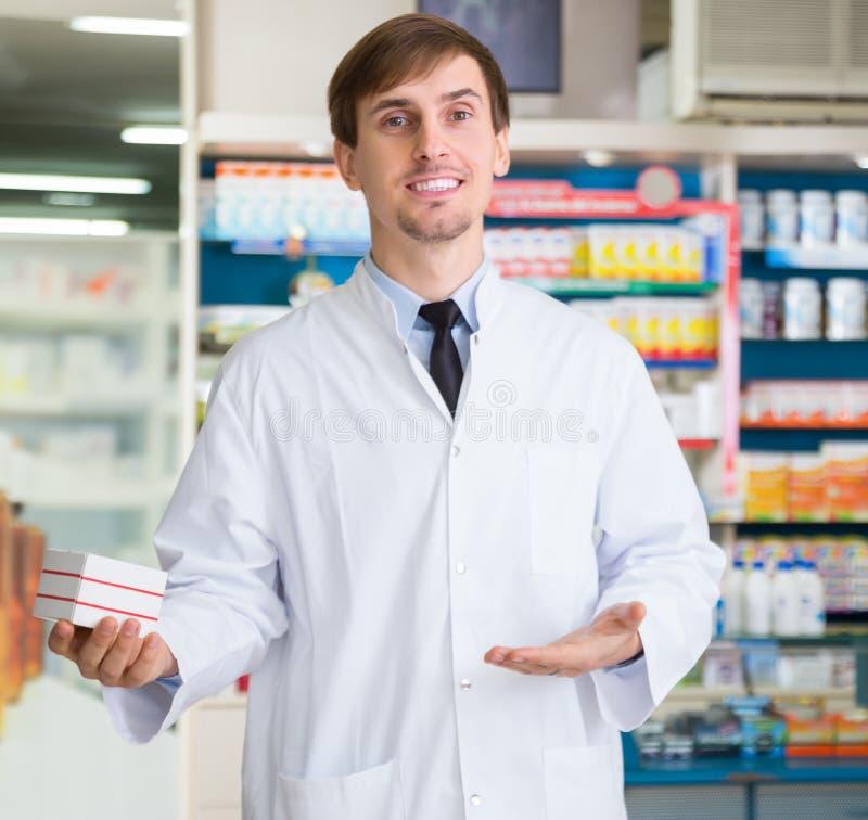 Αρσενική τοποθέτηση φαρμακοποιών στο φαρμακείο στοκ εικόνες