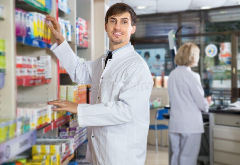 Αρσενική τοποθέτηση φαρμακοποιών στο φαρμακείο στοκ φωτογραφίες με δικαίωμα ελεύθερης χρήσης