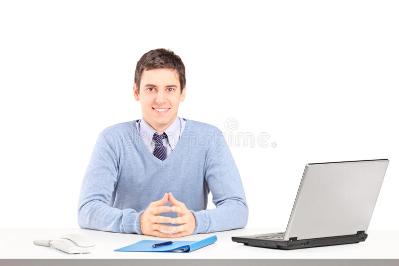 Αρσενική τοποθέτηση χαμόγελου σε ένα γραφείο με το lap-top και άλλο προσωπικό γραφείων στοκ φωτογραφίες με δικαίωμα ελεύθερης χρήσης