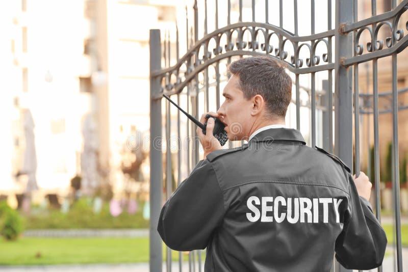 Αρσενική φρουρά ασφάλειας με το φορητό ραδιόφωνο,