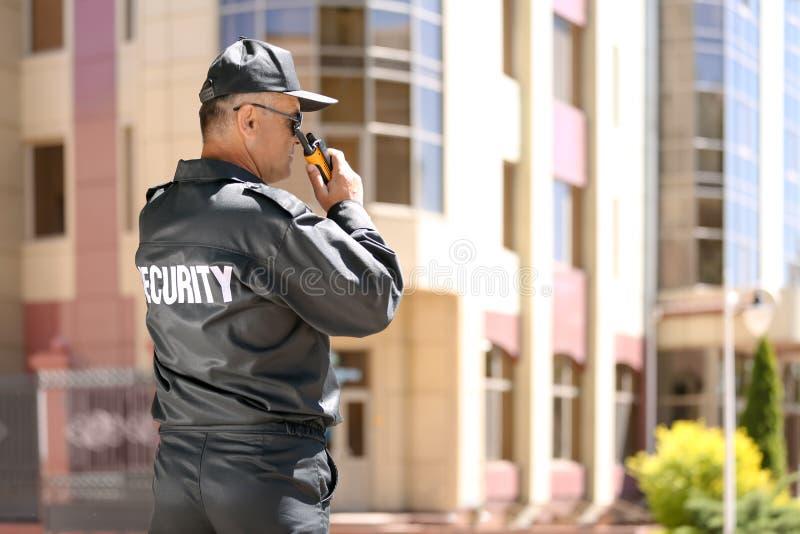 Αρσενική φρουρά ασφάλειας που χρησιμοποιεί τη φορητή ραδιο συσκευή αποστολής σημάτων στοκ εικόνες