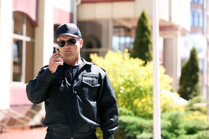 Αρσενική φρουρά ασφάλειας που χρησιμοποιεί τη φορητή ραδιο συσκευή αποστολής σημάτων στοκ εικόνα με δικαίωμα ελεύθερης χρήσης