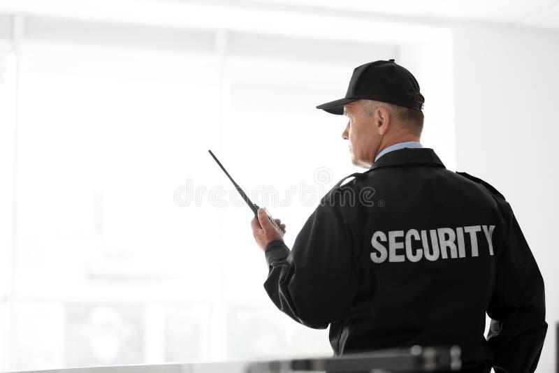 Αρσενική φρουρά ασφάλειας που χρησιμοποιεί τη φορητή ραδιο συσκευή αποστολής σημάτων στοκ φωτογραφίες