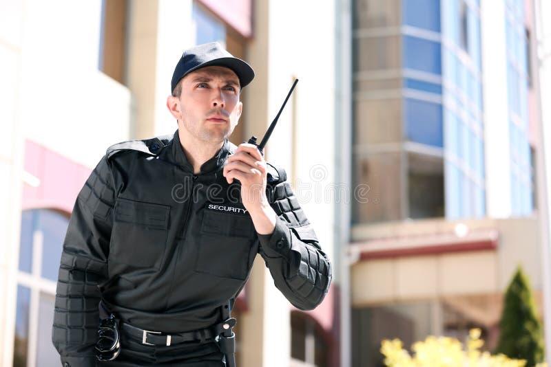 Αρσενική φρουρά ασφάλειας που χρησιμοποιεί τη φορητή ραδιο συσκευή αποστολής σημάτων στοκ φωτογραφία