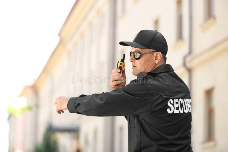 Αρσενική φρουρά ασφάλειας που χρησιμοποιεί τη φορητή ραδιο συσκευή αποστολής σημάτων στοκ εικόνα