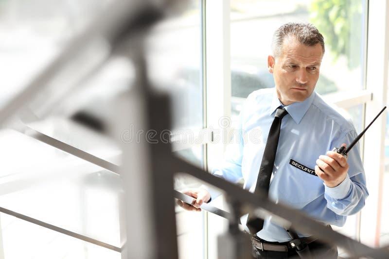 Αρσενική φρουρά ασφάλειας που χρησιμοποιεί τη φορητή ραδιο συσκευή αποστολής σημάτων στοκ φωτογραφία με δικαίωμα ελεύθερης χρήσης