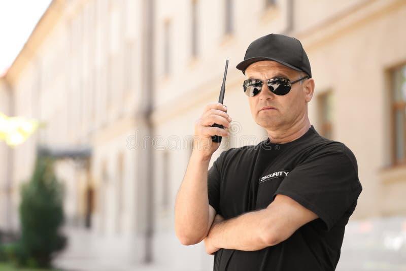 Αρσενική φρουρά ασφάλειας που χρησιμοποιεί το φορητό ραδιόφωνο στοκ φωτογραφία