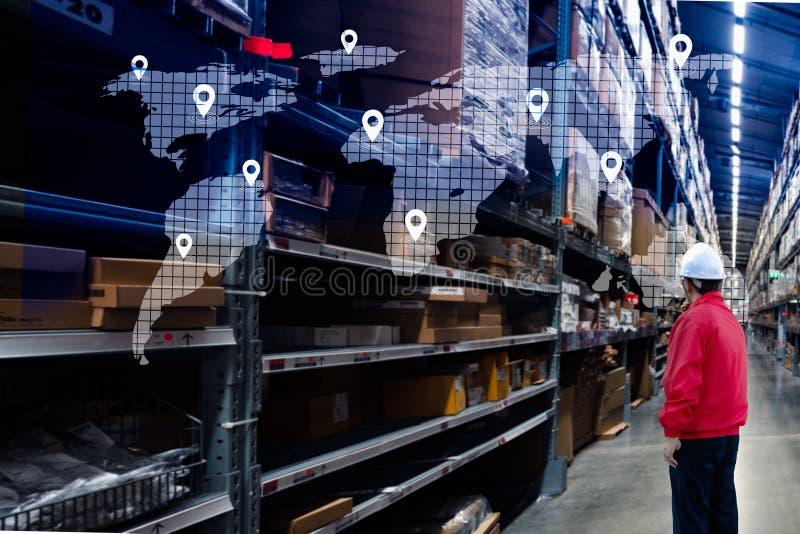 Αρσενική χρησιμοποίηση διευθυντών φορητή σε έναν μεγάλο εργαζόμενο αποθηκών εμπορευμάτων που ελέγχει παραδίδοντας τα κιβώτια Κέντ στοκ φωτογραφία