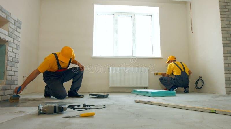 Αρσενικοί εργάτες οικοδομών που καθιστούν τις επισκευές εσωτερικές στοκ εικόνες με δικαίωμα ελεύθερης χρήσης