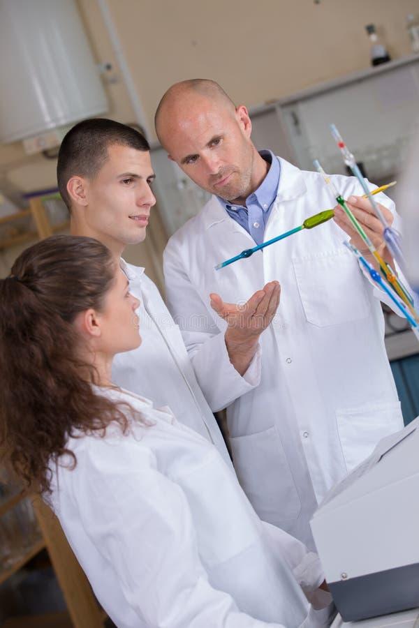 Αρσενικοί ιατρικοί δάσκαλος και σπουδαστές που εκτελούν τη δοκιμή στοκ φωτογραφία