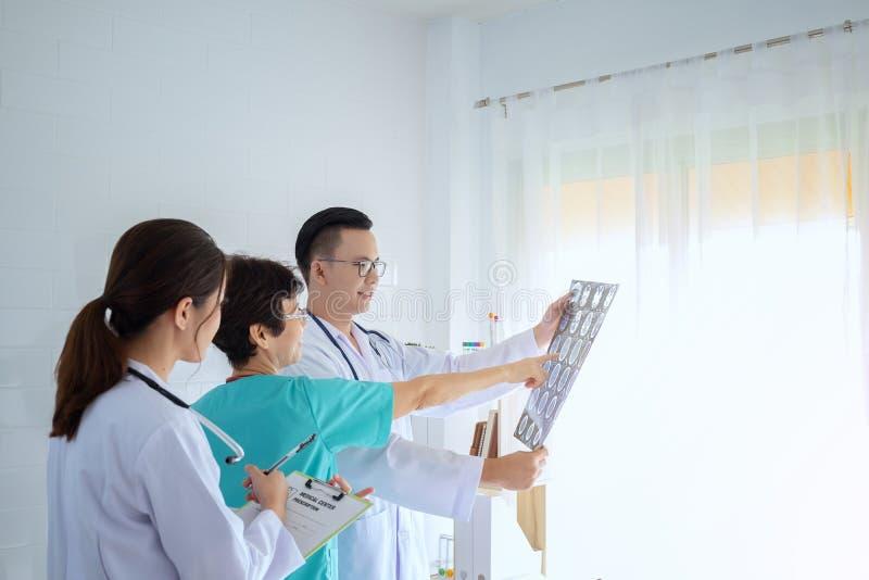 Αρσενικοί και θηλυκοί γιατροί που συμβουλεύονται στο φωτεινό γραφείο, συζήτηση στοκ φωτογραφία