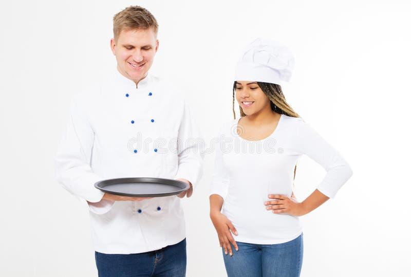 Αρσενικοί και θηλυκοί μάγειρες στον ομοιόμορφο κενό δίσκο λαβής που απομονώνονται στο άσπρο υπόβαθρο στοκ φωτογραφία
