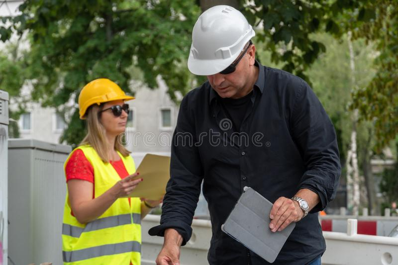 Αρσενικοί και θηλυκοί μηχανικοί στην εργασία για το εργοτάξιο οικοδομής στοκ φωτογραφίες