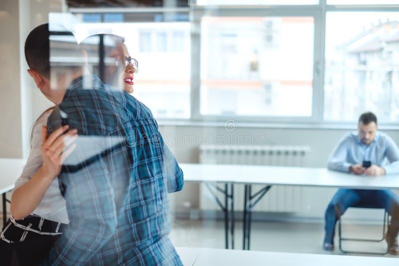 Αρσενικοί και θηλυκοί συνάδελφοι που αγκαλιάζουν πίσω από το γυαλί στοκ φωτογραφίες