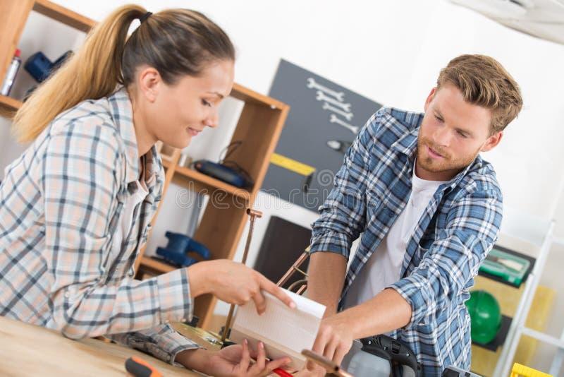 Αρσενικοί και θηλυκοί τεχνικοί που χρησιμοποιούν τη μηχανή στο εργαστήριο στοκ φωτογραφία με δικαίωμα ελεύθερης χρήσης