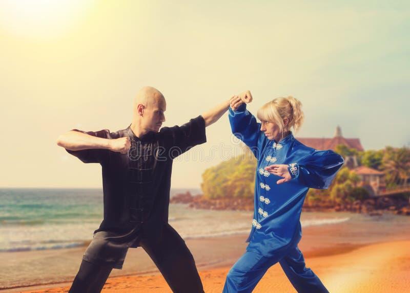 Αρσενικοί και θηλυκοί μαχητές wushu που εκπαιδεύουν στην ακτή στοκ εικόνες