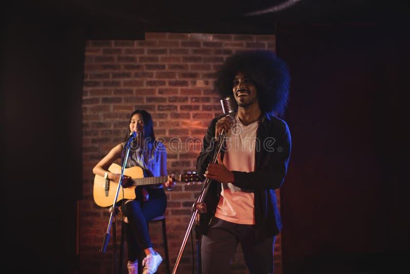 Αρσενικοί και θηλυκοί τραγουδιστές που αποδίδουν στο νυχτερινό κέντρο διασκέδασης στοκ εικόνα με δικαίωμα ελεύθερης χρήσης