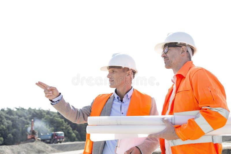 Αρσενικοί μηχανικοί που συζητούν στο εργοτάξιο οικοδομής ενάντια στο σαφή ουρανό στοκ εικόνες